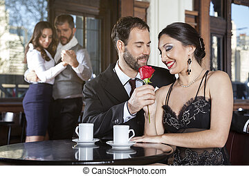 Romantic Couple Holding Rose While Dancers Performing Tango...