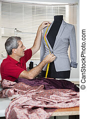 Tailor Measuring Suit On Mannequin - Mature male tailor...