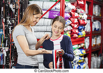 Mother And Daughter Shopping At Pet Store - Smiling mother...