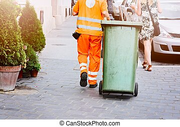 Worker of cleaning company in orange uniform with a green...