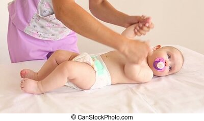 The doctor makes the massage a little baby.