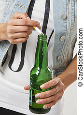 Underage activities - close up of a teenage girl putting a...