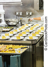 Serving Cake in Commercial Kitchen - Worker plating cake in...