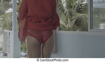 Woman getting dressed in apartment - Back view of beautiful...