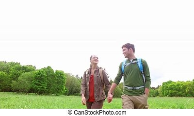 happy couple with backpacks walk on country road