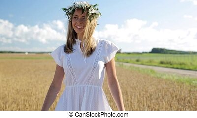happy young woman in flower wreath on cereal field -...