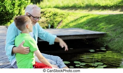 grandfather and grandson sitting on river berth - family,...