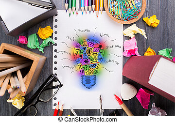 Colorful lightbulb sketch - Top view of messy desktop with...