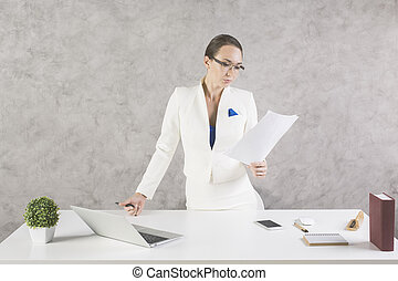 Woman with paperwork in hand standing at white office desk...