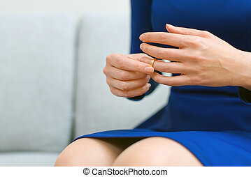 Divorce concept Woman taking off wedding ring