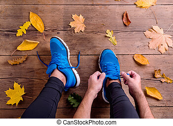 Unrecognizable runner in sports shoes tying shoelaces Autumn...