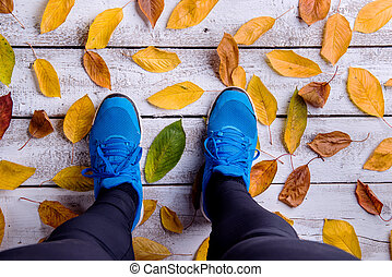 Legs of runner. Blue sports shoes. Colorful autumn leaves....