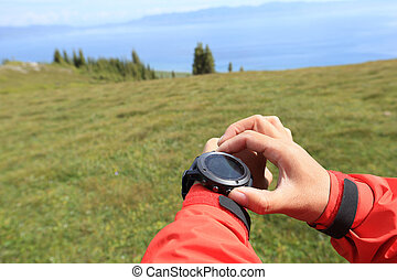 young woman hiker checking the altimeter on sports watch at...