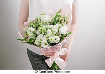 Florist at work. Make bouquet of white lisiantus . Vintage...