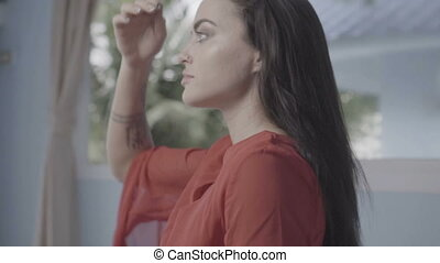 Woman in red dress adjusting hair - Closeup portrait of...