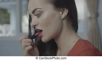 Beautiful woman applying lipstick - Closeup of beautiful...
