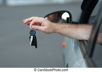Mens hand holding a key from the car, symbolize joy purchase...