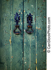Double Green Door - Two black door handles in old green...