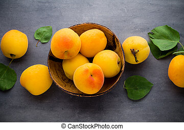 Fresh apricots in wooden bowl on old rustic background