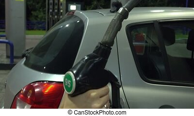 Girl refueling the car at gas station. Inserting and...