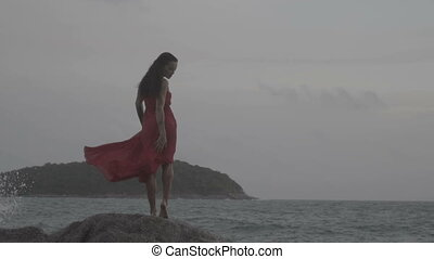 Beautiful seductive woman in red dress enjoying herself on rocks by the sea