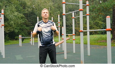 Man doing workout on the playground, early in the morning