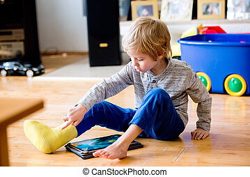 Boy with broken leg in cast playing on tablet. - Cute little...