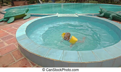 Little Girl Swims in Small Round Pool by Umbrellas at Hotel