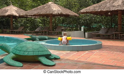 Little Girl Climbs into Swimming Pool by Umbrellas at Hotel