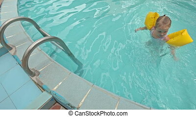 Little Girl Comes out of Pool with Ladder against Water-slide