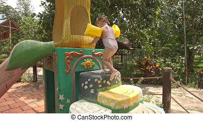 Little Girl Climbs up Water-slide by Steps Sits down at Pool...