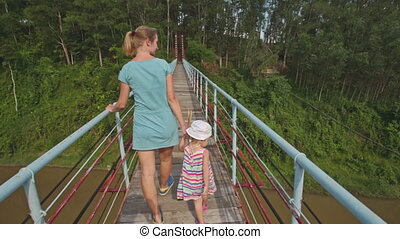 Mother Leads Small Girl by Hand along Bridge over River -...