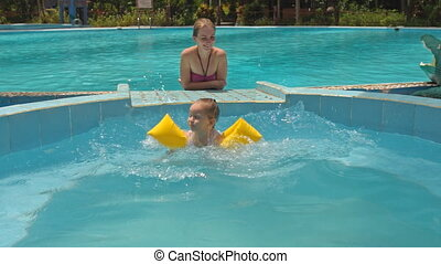 Little Girl Jumps into Pool Mother Looks at Hotel