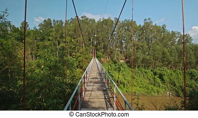 Camera Moves along Suspension Bridge over River in Park -...