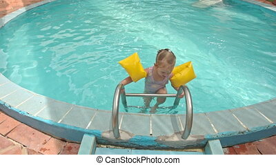Little Girl Comes out of Pool with Ladder to Poolside