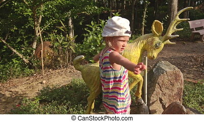 Small Girl Climbs on Deer Sculpture in Tropical Park - small...