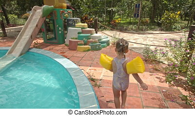 Little Girl Walks Climbs up Water-slide by Steps at Pool