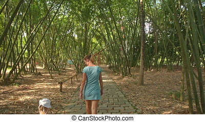 Mother Leads Small Girl by Hand along Path under Tree Shadow