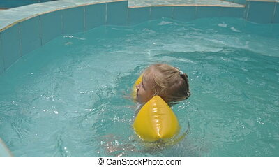 Little Blond Girl in Yellow Arm-bands Swims in Pool at Hotel...