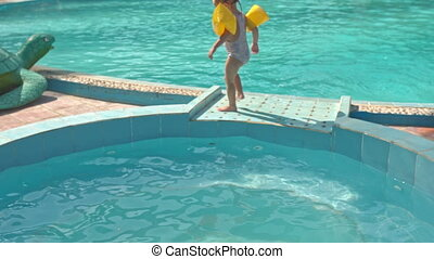 Little Girl Walks on Barrier Jumps into Pool by Toy Turtle