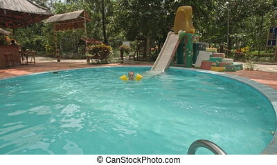 Little Girl Slides down from Water-slide into Pool Blue Water