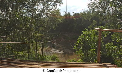 View of Zipline Attraction with Person in Tropical Park -...
