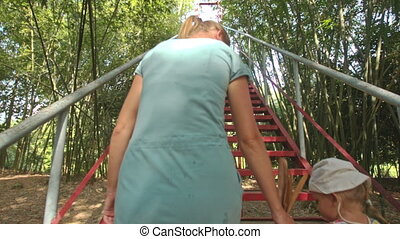 Mother Leads Small Girl by Hand up Staircase under Tree...