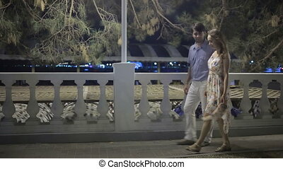 Couple Walking Along Street On Night Out lovely romantic...