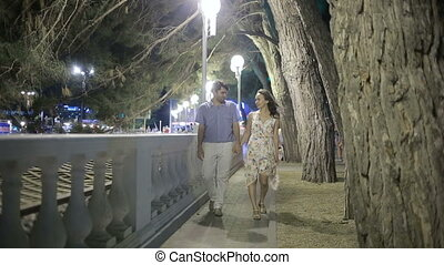 Couple Walking Along Street On Night Out. lovely romantic...