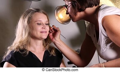 Professional face makeup - Female makeup artist brushing...