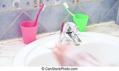Woman brushing teeth in bathroom - Close up of water tap in...
