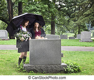 Young Mourners - Two young girls visiting a gravesite in the...