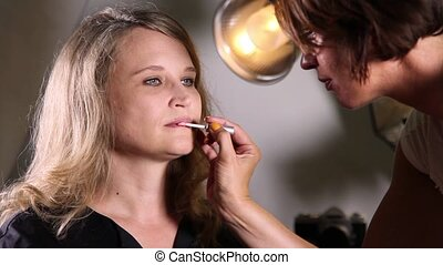 Makeup before a shoot - Professional makeup artist paints a...