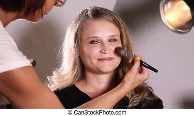 Makeup artist working with a model - Professional makeup...